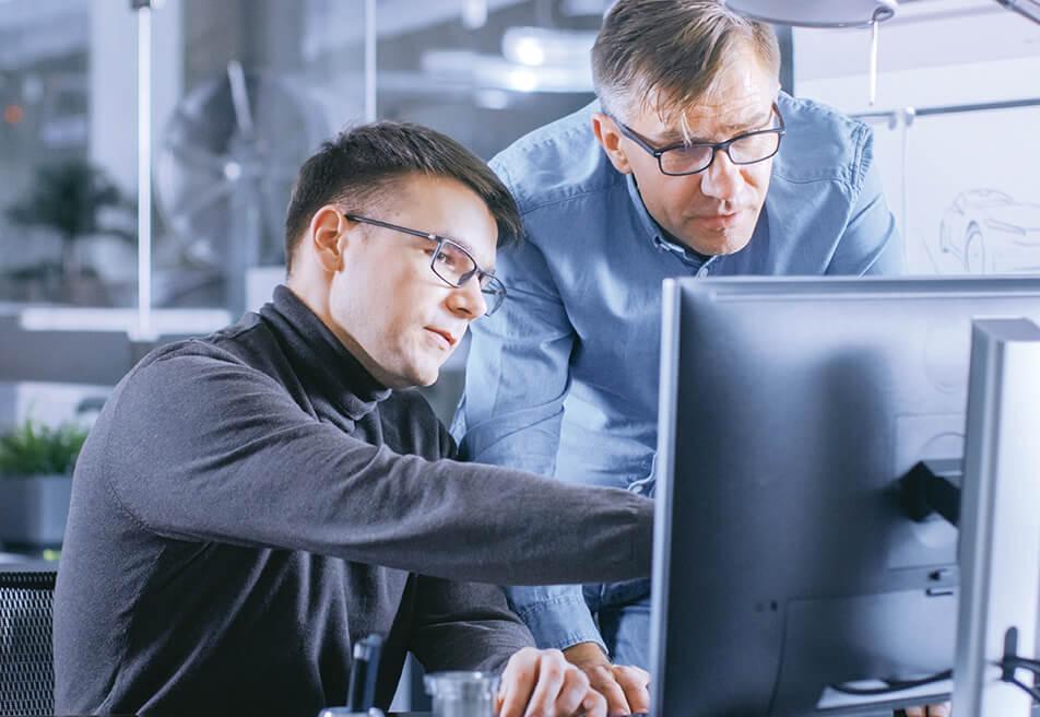 INTEGA-Mitarbeiter im Gespräch am Rechner